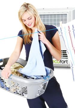 Hübsche Frau hängt Wäsche auf - im Hintergrund ein ecofort Raumluftwäschetrockner